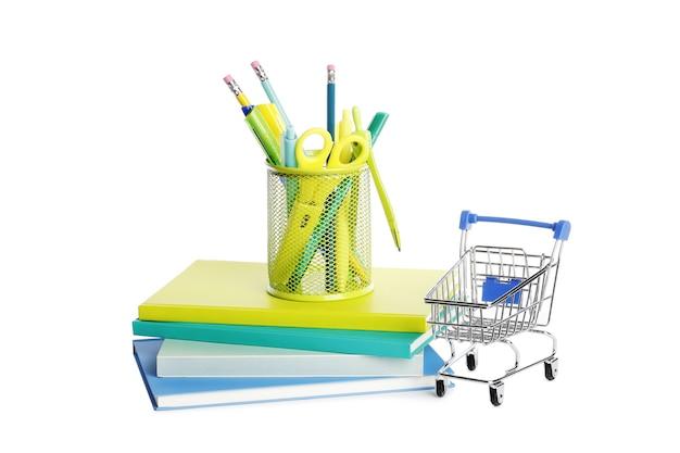 Materiale scolastico con carrello della spesa su sfondo bianco