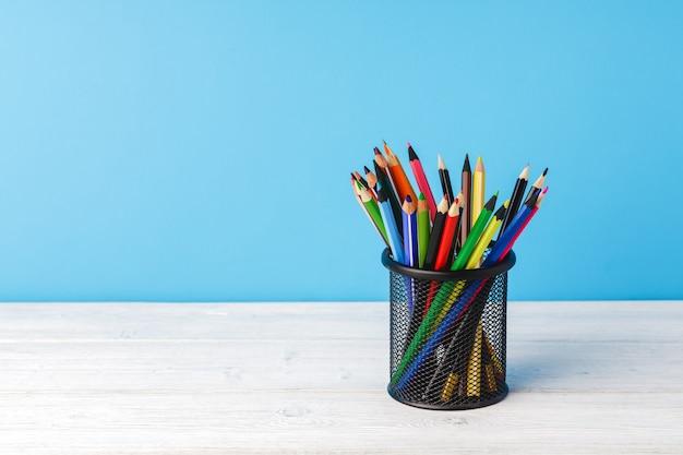 Forniture scolastiche sulla scrivania in legno su sfondo blu vista frontale