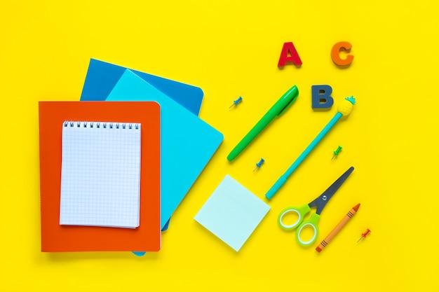 Materiale scolastico su sfondo giallo diversi articoli di cancelleria con uno spazio vuoto su una scrivania gialla