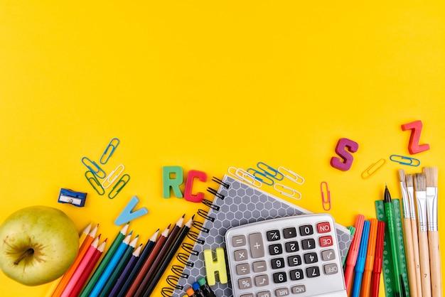 Materiale scolastico su sfondo giallo
