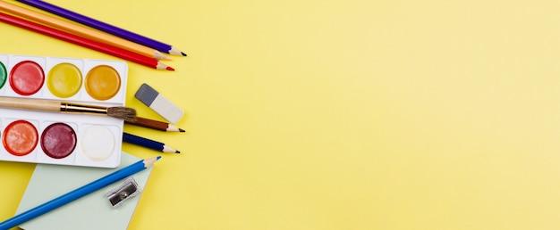 Forniture scolastiche su uno sfondo giallo.