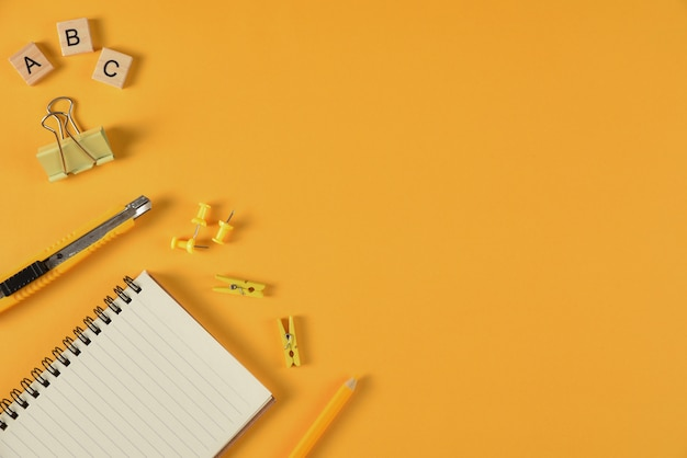 Rifornimenti di scuola su fondo di carta giallo con copyspace. istruzione o concetto di ritorno a scuola.