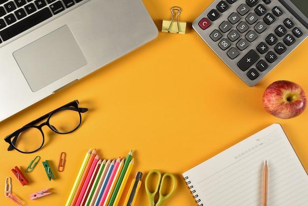 Rifornimenti di scuola su carta gialla con copyspace. istruzione o concetto di ritorno a scuola.