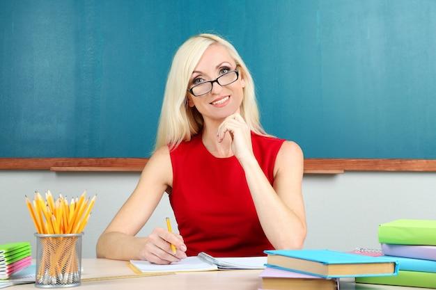 Insegnante di scuola seduto al tavolo sulla lavagna