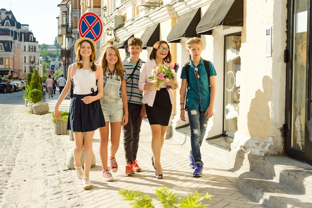 Maestro di scuola con bouquet di fiori e studenti di gruppo