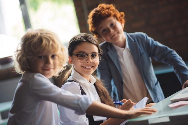 A scuola. tre simpatici bambini che studiano in classe e si sentono eccitati