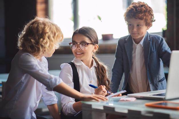 A scuola. tre bambini carini che lavorano insieme alle lezioni