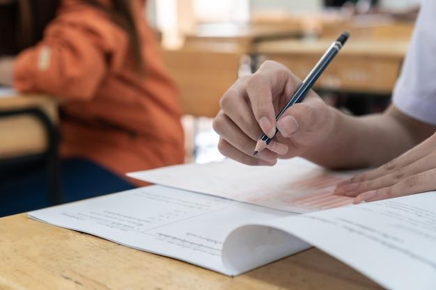 Mani di studenti universitari della scuola che prendono gli esami, scrivendo aula d'esame