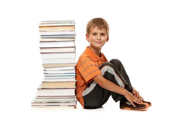 Scolaro e libri isolati su un bianco