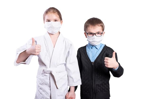 Scolaro ragazzo e ragazza atleta mostrano i pollici in su mascherato isolato su sfondo bianco