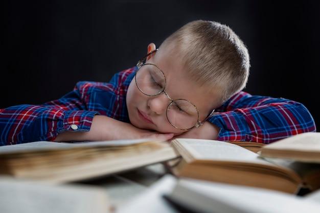 Ragazzo scolaro con gli occhiali dorme sui libri. muro nero. apprendimento a distanza durante la pandemia di coronavirus.