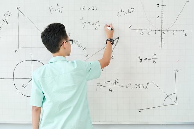Scolaro in equazione della geometria di scrittura di vetro sulla lavagna, vista dal retro