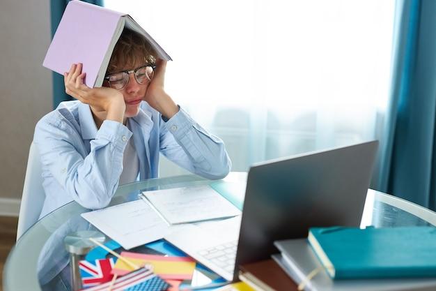 Scolaro sta scrivendo il rapporto sul laptop, facendo i compiti