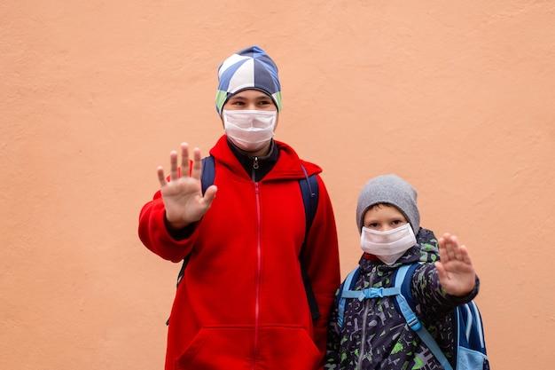 Uno scolaro con una maschera protettiva mostra la sua mano stop