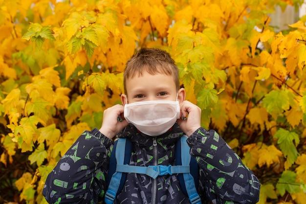 Lo scolaro in maschera protettiva per strada