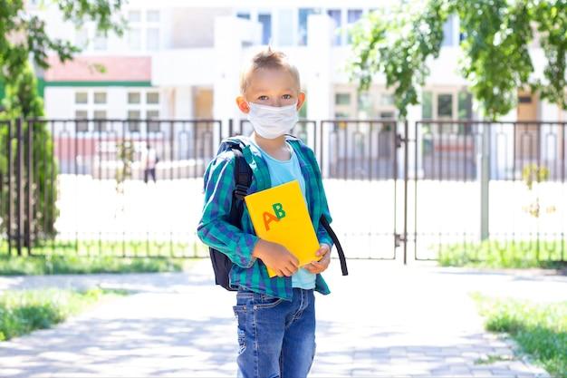 Scolaro in maschera protettiva con uno zaino e un libro di testo in mano. in una maglietta e una camicia a quadri