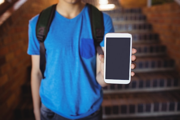 Scolaro in piedi con lo zainetto che mostra il telefono cellulare vicino alla scala a scuola