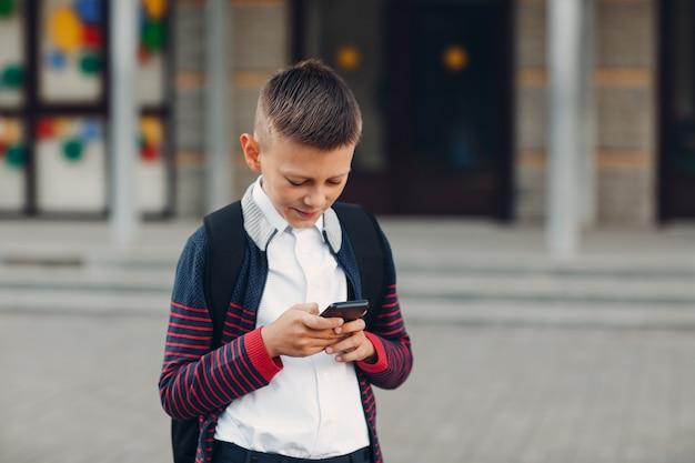 Ragazzo adolescente scolaro con telefono cellulare in piedi a scuola sullo sfondo