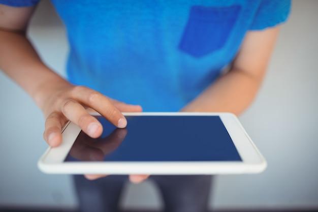 Scolaro con tavoletta digitale nel corridoio a scuola