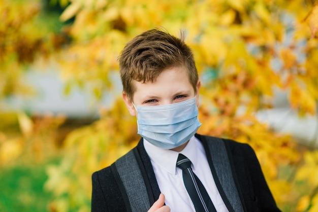 Scolaro esce da scuola indossando una maschera protettiva in città