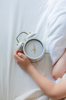 Scolaro con sveglia che dorme nel letto. mattina.