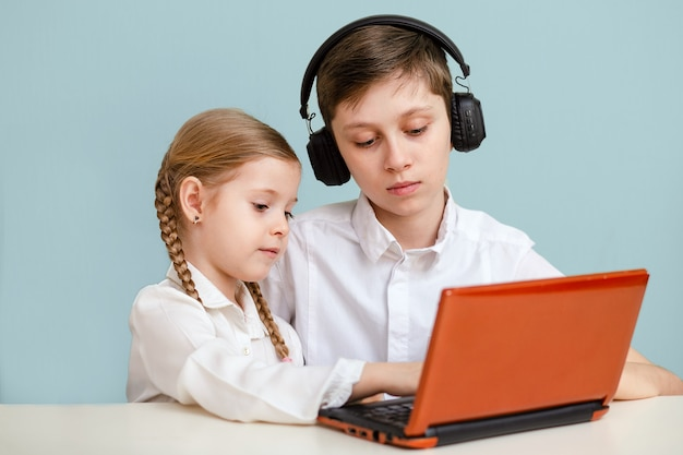 Scolaro con le cuffie e una ragazza che studia a casa con un computer portatile digitale e fa i compiti.