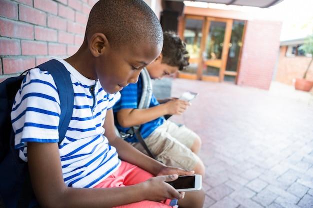 Scolari che utilizzano i telefoni cellulari nel corridoio a scuola