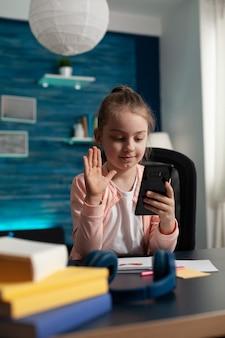 Scolaro che saluta un amico remoto durante la conferenza della riunione di videochiamata online