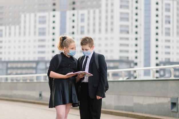 Scolari, un ragazzo e una ragazza con maschere mediche camminano per la città.