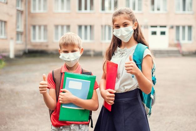 Scolari in maschere mediche prima delle lezioni che mostrano i pollici in su