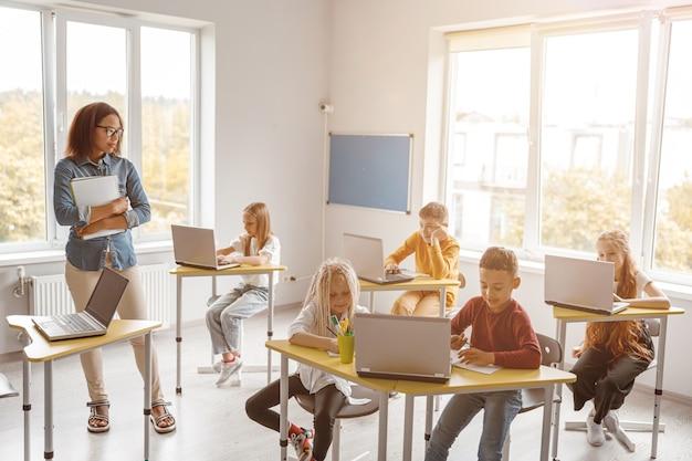 Scolari seduti alle scrivanie che usano i laptop