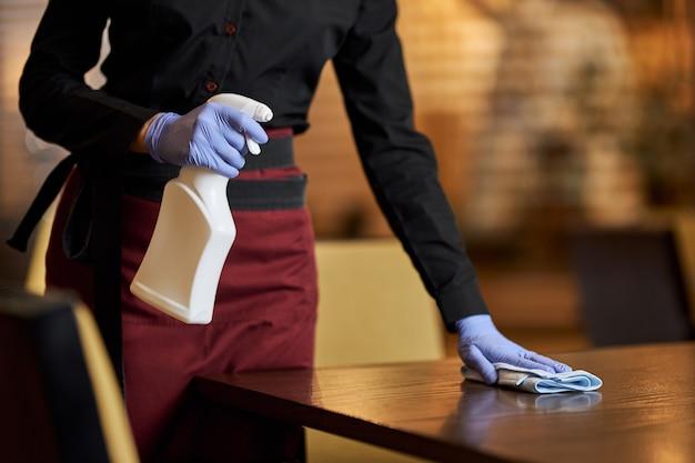Cameriera istruita che disinfetta regolarmente la superficie del tavolo con uno spray speciale