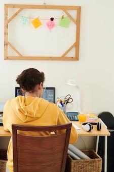 Studentessa che fa i compiti per la lezione di programmazione alla sua scrivania a casa