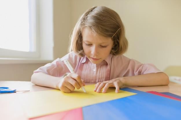 Scrittura del disegno della scolara a penna su carta colorata.