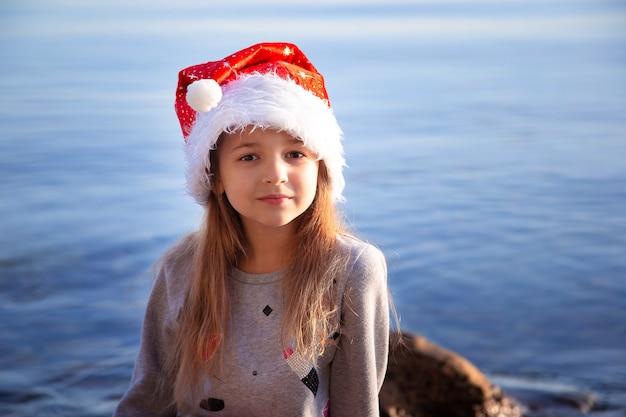 Una studentessa con il cappello di capodanno si siede in riva al mare. natale nei paesi caldi. vacanze e capodanno al mare