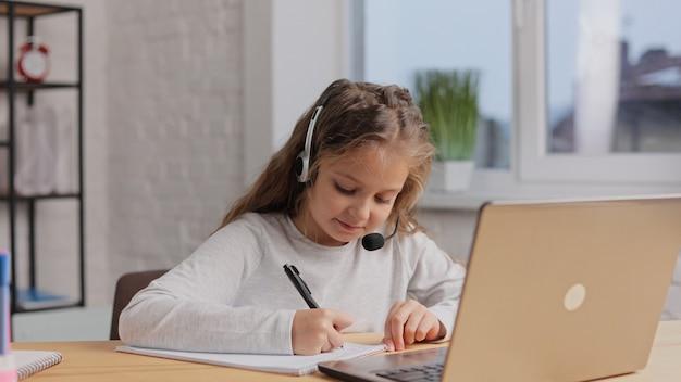 Studentessa in cuffia ha lezione online, videochiamata con l'insegnante. ragazza carina della scuola primaria studiando a casa utilizzando il computer portatile.