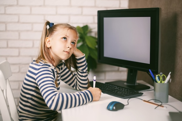 La studentessa è seduta al tavolo, pensierosa e guarda in alto