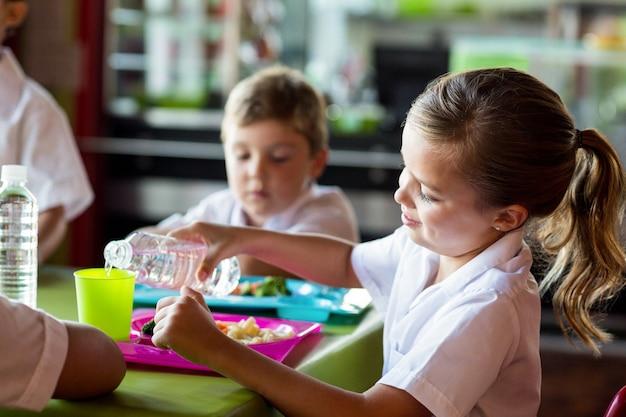 Acqua di versamento della scolara in bicchiere