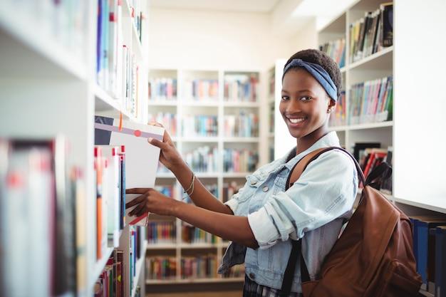 Studentessa selezionando libro da scaffale in biblioteca a scuola