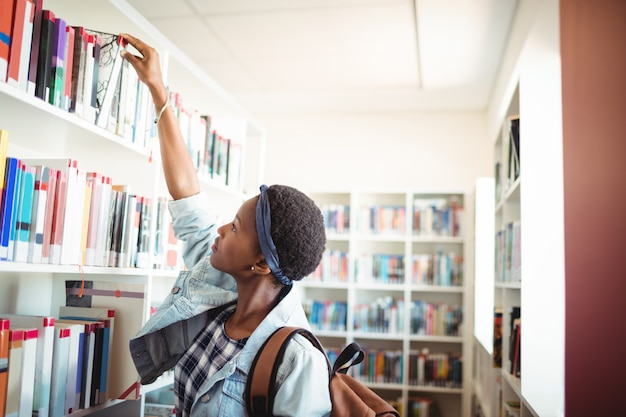 Studentessa selezionando libro da scaffale in libreria