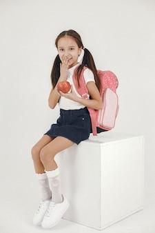 La scolara si siede sul cubo bianco. ragazza con lo zaino.