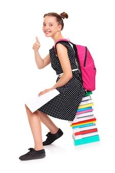 Una studentessa seduta su una pila di libri