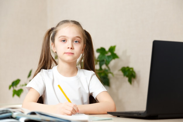 Studentessa che studia i compiti durante la sua lezione online a casa, istruzione online e concetto di scuola online, scolaro a casa. apprendimento a distanza o remoto