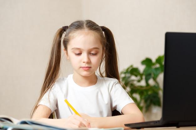 Studentessa che studia i compiti durante la sua lezione online a casa, istruzione online e concetto di scuola online, scolaro a casa