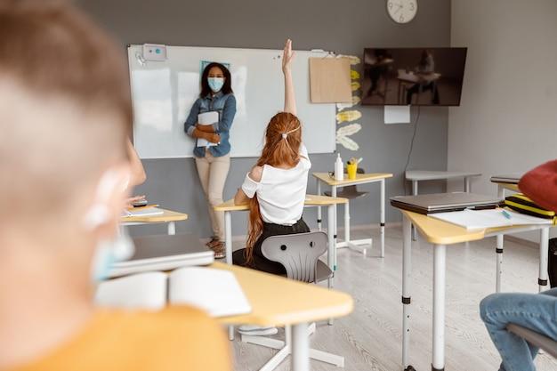 Studentessa che vuole rispondere alla lezione e guarda l'insegnante