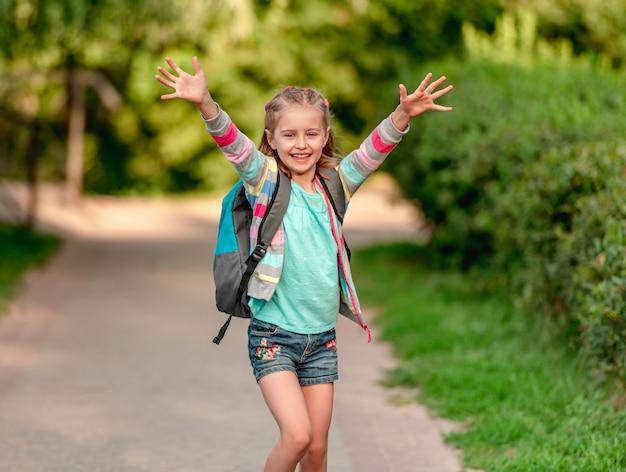 Studentessa con lo zaino che va a scuola con le mani in alto sullo sfondo del parco