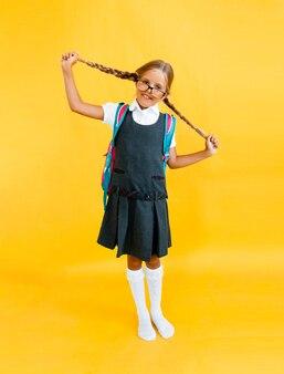La scolara con lo zaino sta e salta sul fondo giallo dello studio