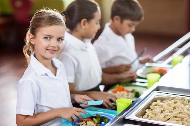 Scolara con il compagno di classe che sta vicino al contatore della mensa