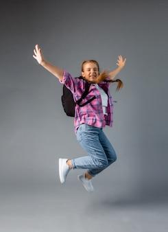 Studentessa con rbkzak che salta su uno sfondo grigio. contenuto scolastico