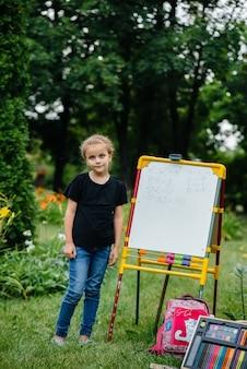 Una studentessa scrive lezioni su una lavagna ed è impegnata in una formazione all'aperto
